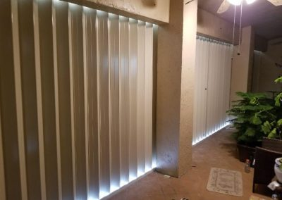 White accordion shutters in an entrenched track in an enclosed patio with columns and ceiling fan.