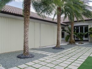 Single story Miami home yard with palm trees and windows showing closed beige Genesis accordion shutters.